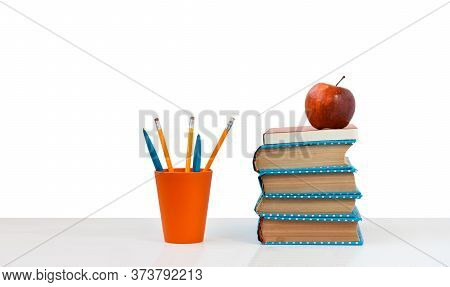 Back To School, Pile Of Books And Red Apple On The White Table With White Background. Distance Home