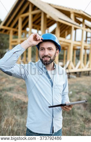 Portrait Of An Architect Or Builder With Digital Touchpad In Front Of The Wooden House Structure. Bu