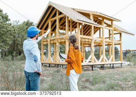 Builder With A Female Client Near The Wooden House Structure On The Construction Site Outdoors. Buil