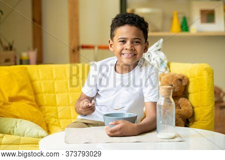 Cute happy little boy of African ethnicity looking at you with toothy smile while sitting on couch and eating cornflakes with milk for breakfast