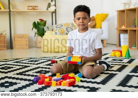 Adorable little kid of African ethnicity looking at you while sitting on carpet with black-and-white decor and playing leisure game in living-room