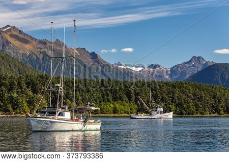 Fishing Boat Sailing In Harbor And Another Fishing Boat Drifting Behind It. Mountains, Forest And Bl