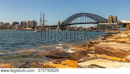 Panoramic View Of Sydney Harbor Bridge And Downtown Buildings. Sailboat Sailing In The Harbor Toward