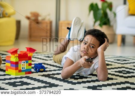 Bored and unhappy cute little boy of African ethnicity pushing button of remote control while lying in front of tv set at home