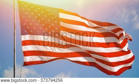 American Flag Blowing In The Wind With A Blue Sky Background And Lens Optical Flare. Usa American Fl