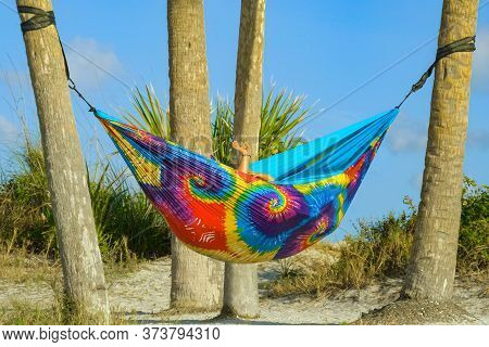 Lesbian Couple Relaxing In Rainbow Hammock At Sunset. Two Lesbians Hid In A Cozy Hammock Of Rainbow