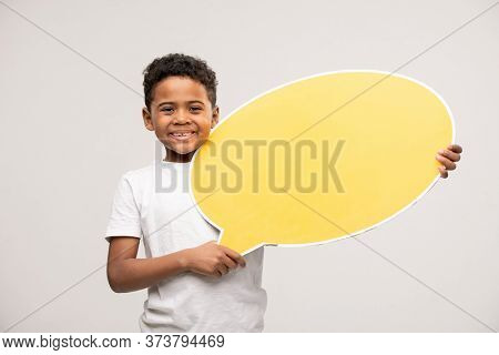 Cheerful little boy of African ethnicity looking at you with toothy smile and showing blank yellow speech bubble against white background