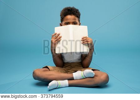Cute little schoolboy of African ethnicity holding open book close to his face and peeking out of its cover while sitting on the floor