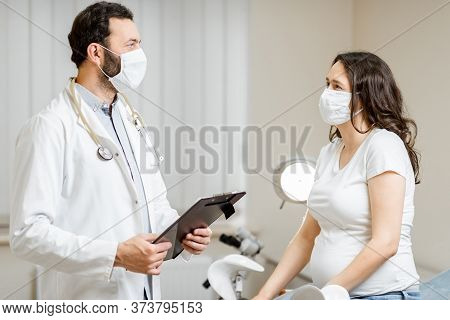 Doctor With A Pregnant Woman In Medical Masks During An Examinations. Concept Of New Rules For The U