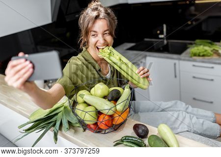 Young Woman Making Selfie Photo Or Vlogging On Mobile Phone About Healthy Eating, Sitting With Raw I
