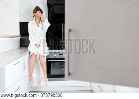Woman In Bathrobe Sitting On The Kitchen With Opened Fridge On The Foreground, Feeling Hungry At Nig
