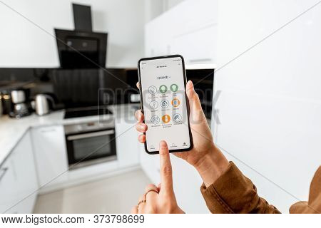 Woman Controlling Kitchen Appliances With A Smart Phone, Close-up On Mobile Device With Launched Sma