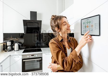 Young Woman Controlling Kitchen Appliances With A Digital Tablet On The Wall With Launched Smart Hom