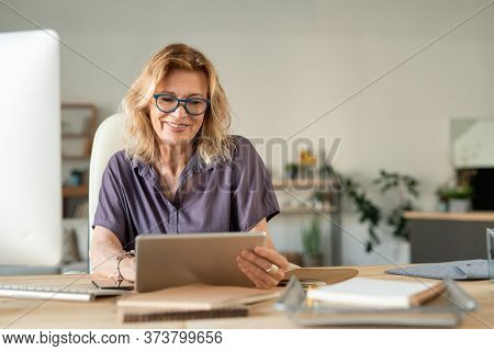 Smiling mature businesswoman using touchpad to surf in the net for online data while sitting by table and working in home environment