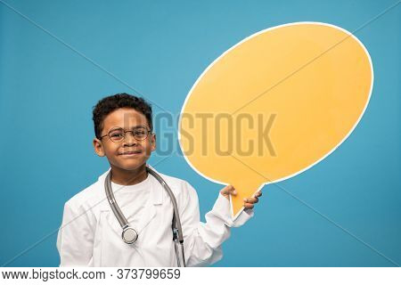Cute little African or mixed-race doctor in eyeglasses and whitecoat holding blank yellow paper speech bubble in isolation