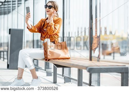 Young Woman Having A Video Call On Mobile Phone While Sitting At The Transport Stop Outdoors. Online