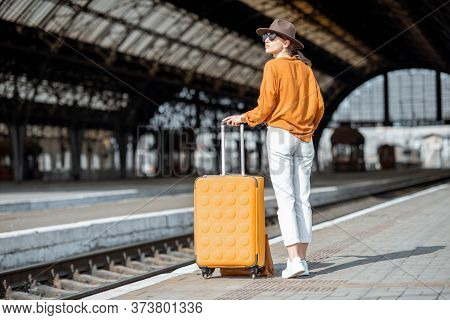 Young Female Traveler Standing With A Suitcase At The Old Train Station Alone. Travel Concept