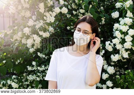 Portrait Of  Young Woman Corrects  Protective Mask On Her Face. In Background Is Flowering Plant. Co