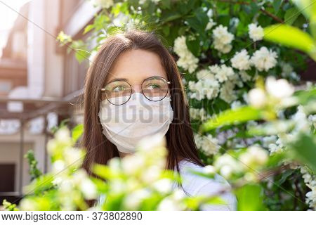 Portrait Of Young Woman In Protective Mask On Her Face. In Background Is  Flowering Plant And Buildi