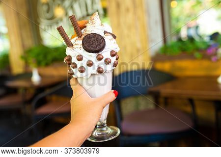 Cool Milkshake With Cookies And Chocolate Balls. Milkshake In A Glass Beaker On A Table On A Street