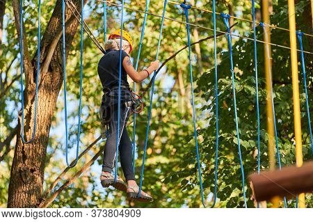 Girl In High Ropes Experience Adventure Tree Park. Rope Road Course In Trees. Climbing Adventure Rop