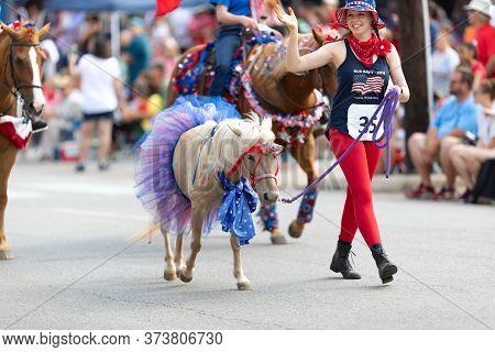 Arlington, Texas, Usa - July 4, 2019: Arlington 4th Of July Parade, Young Woman Leading A Pony Down
