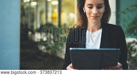 Female Banker Using Tablet And Wireless Earphones Outdoors Near Office Background Lights, Portrait Y