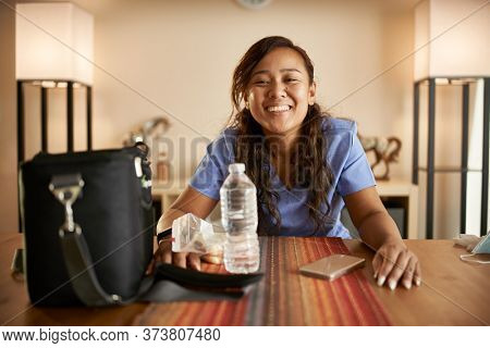 happy filipina nurse at home packing lunch portrait
