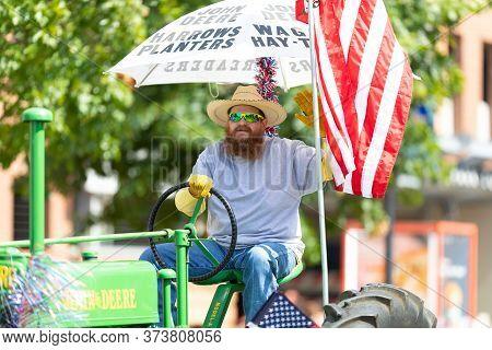 Arlington, Texas, Usa - July 4, 2019: Arlington 4th Of July Parade, Man Driving An Old Tractor At Ce