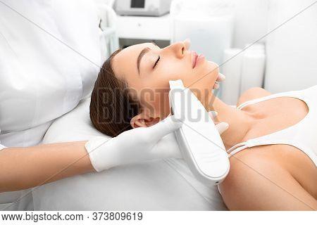 Woman Getting Ultrasonic Peel Skin, A Cleansing Procedure Using A Special Device. Procedure Ultrason