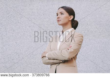 Portrait Beautiful Young Business Woman In Suit Keep Arms Crossed And Look On Copy Space Gray Backgr