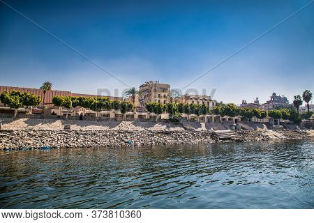 Luxor, Egypt - Jan 28, 2020: Residential buildings on the Nile river with sailboats in Luxor, Egypt