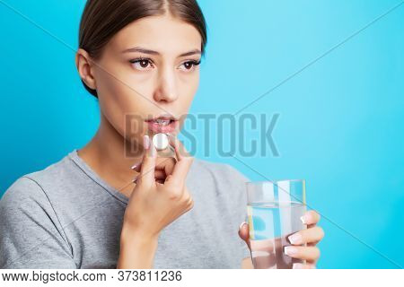 An Exhausted Woman Suffering From Toothache Takes A Painkiller