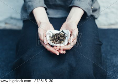 Dry Tea Leaves In A White Saucer. Unrecognizable Woman Holding A Bowl Of Tea In His Hands Showing It
