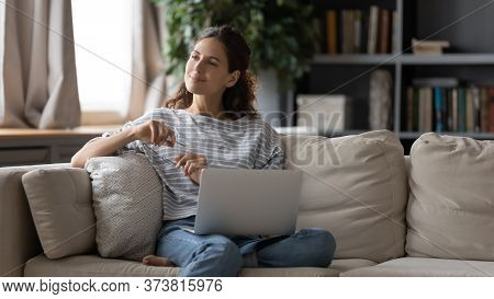 Dreamy Woman Taking Off Glasses, Pondering Ideas, Sitting On Couch