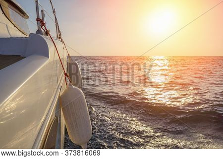 The Yacht At Sunset. Sailing Boat In The Sea During Sunset. Yachting As A Luxury Sport And Great Vac