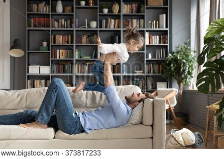Smiling Father Holding Little Daughter Pretending Flying, Playing Funny Game