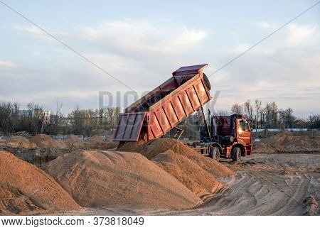 Dump Truck Unloading Earth Sand For Road Construction Or For Foundation Work.