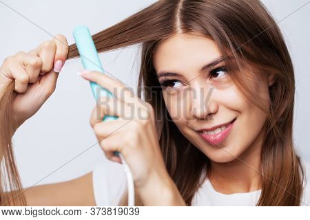 Beautiful Young Woman Uses A Hair Straightener To Make A Beautiful Styling