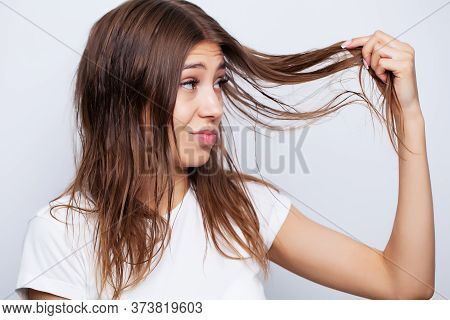 Beautiful Young Female Model Takes Care Of Her Hair And Uses A Hair Straightener