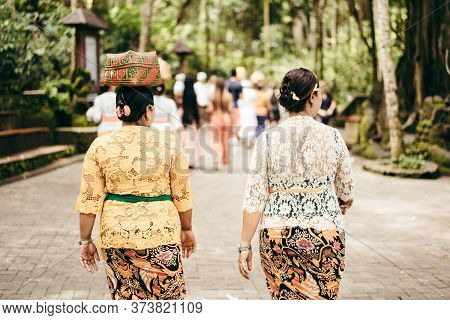 Women In Festive Clothes Going To The Temple With An Offering To The Gods On Their Heads. Bali, Indo
