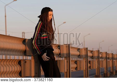 Sad Girl With Dreadlocks In Black Sportswear Stands On The Road At Sunset