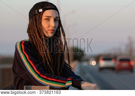 Pensive Girl With Dreadlocks In A Black Cap Stands On The Road