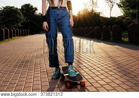 Slender Girl With Dreadlocks In Jeans And A Top Rides A Longboard At Sunset