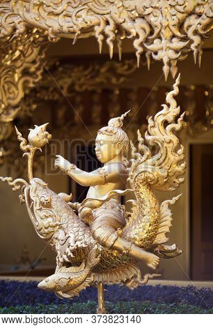 Chiang Rai, Thailand - November 15, 2019: Golden Colored Statue In Thay Style - Boy Riding A Fish Dr