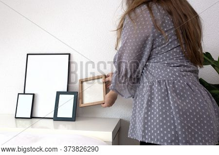 Woman Holding Empty Photo Or Picture Frame In A Modern Room Near White Wall, Scandinavian Design, Re