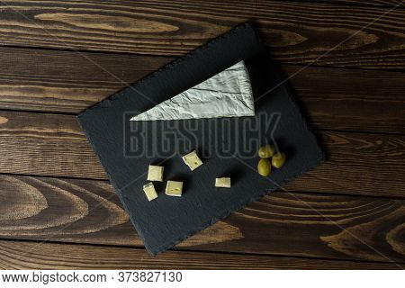 Camembert Cheese. Cheese Dish With Olives On An Old Black Wooden Table. Brie Cheese. Food For Wine A