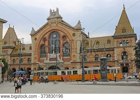 Budapest, Hungary - July 13, 2015: Central Market Hall At Fovam Square With People And Tram Public T