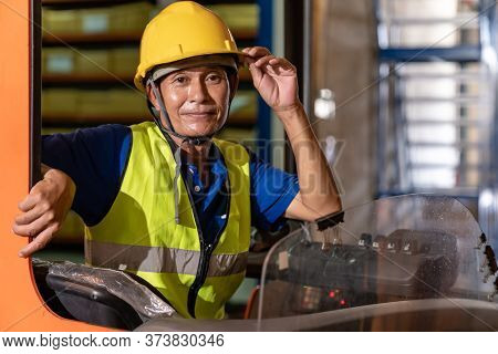 Portrait asian male warehouse worker using forklift truckin large warehouse distribution center. Business warehouse storage transportation and logistic concept