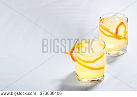 Summer Refreshing Cocktails, Lemonade Or Mojito With Orange Zest And Ice In A Glass On White Backgro